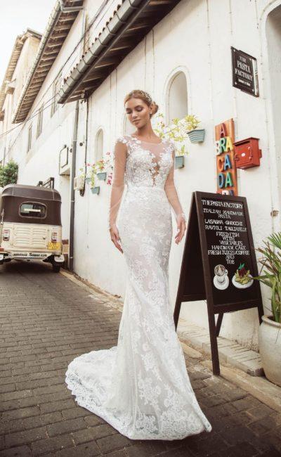 Прямое свадебное платье с кружевным декором и прозрачным рукавом.