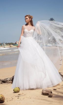 Пышное свадебное платье с полупрозрачной тканью над корсетом.