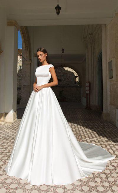 Атласное свадебное платье с закрытым лифом и вырезом на спине.
