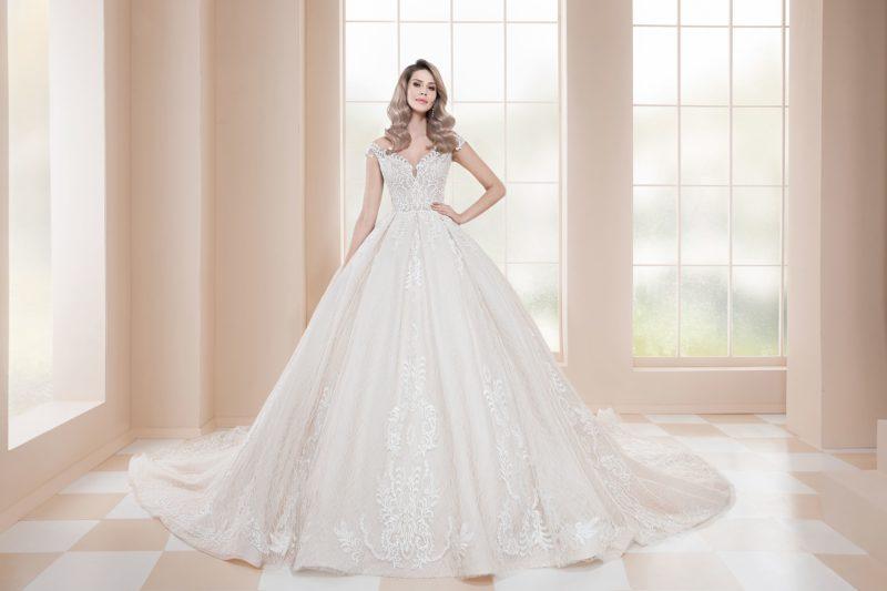 Пышное свадебное платье цвета слоновой кости с белой кружевной отделкой.