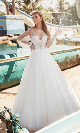 Свадебное платье с отделкой из бусин и длинным прозрачным рукавом.
