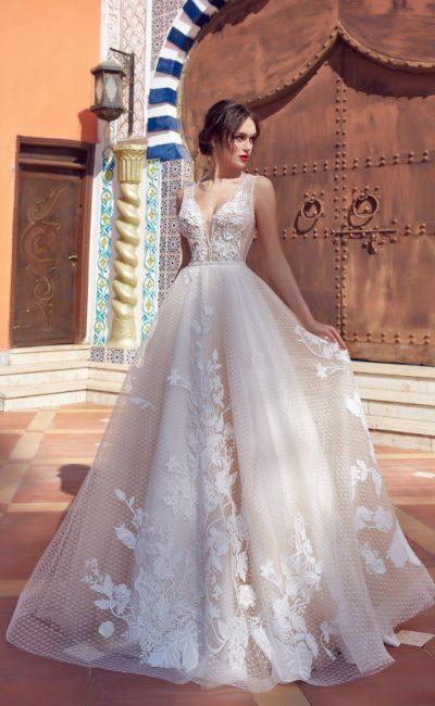 Пышное свадебное платье с сетчатым верхом подола и глубоким вырезом на лифе.