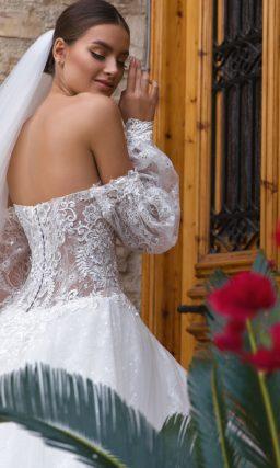 Пышное свадебное платье с портретным декольте и широким рукавом.