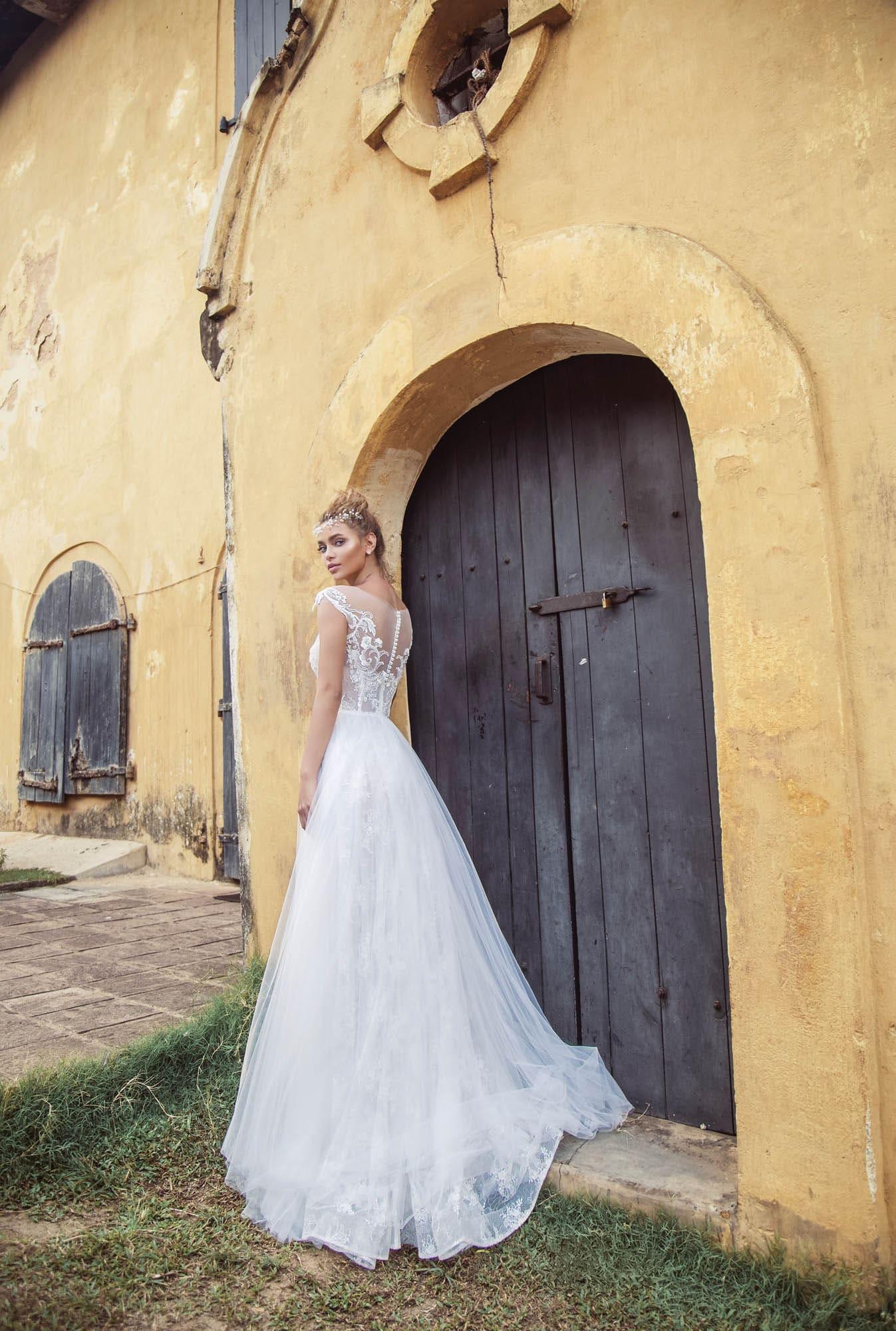 Воздушное свадебное платье с тонкой вставкой над лифом и коротким рукавом.