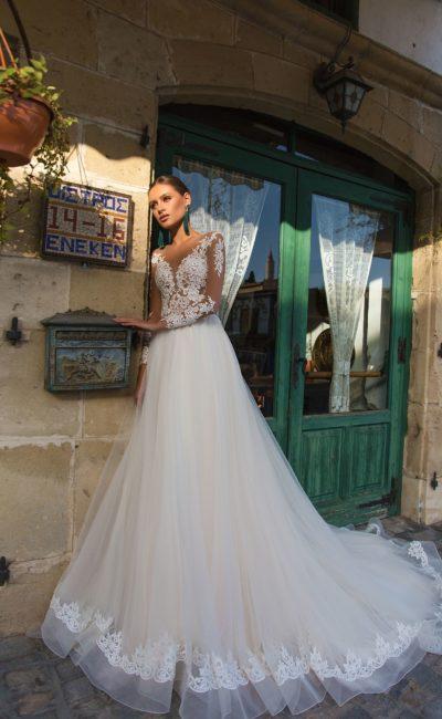 Свадебное платье с длинным рукавом и многослойной юбкой со шлейфом.