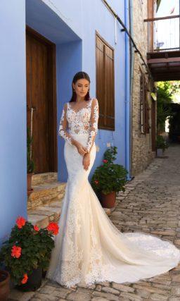 Облегающее свадебное платье с длинным прозрачным рукавом и кружевным декором.
