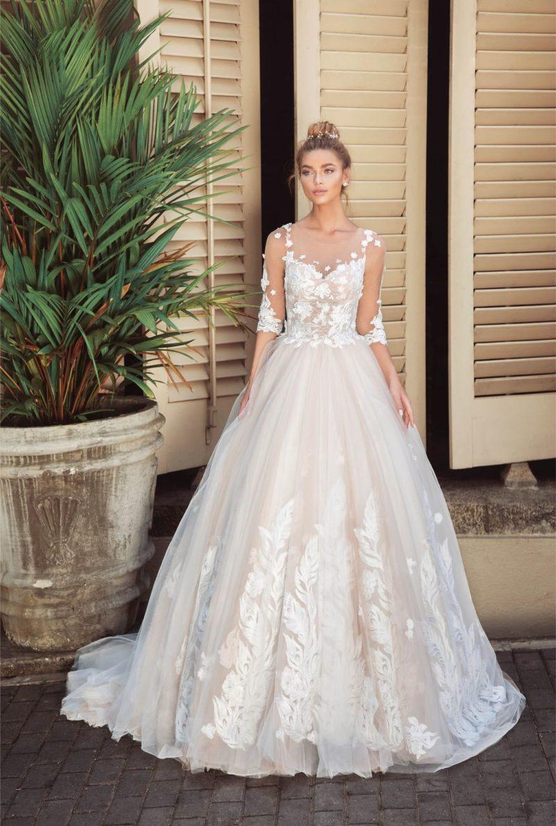 Пудровое свадебное платье пышного кроя, покрытое белым кружевом.