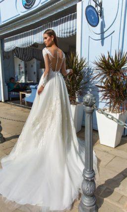 Пышное свадебное платье с кружевным декором и длинным прозрачным рукавом.