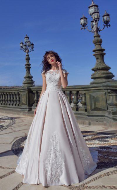 Роскошное свадебное платье с коротким рукавом и пышной юбкой.