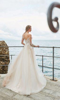 Воздушное свадебное платье с кружевной отделкой и персиковым оттенком ткани.