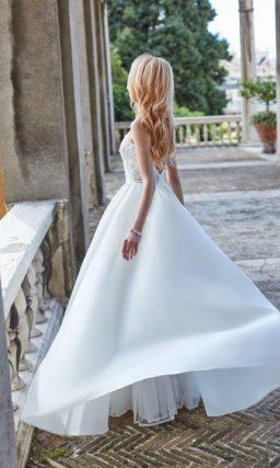 Свадебное платье с облегающим верхом и юбкой с коротким шлейфом.