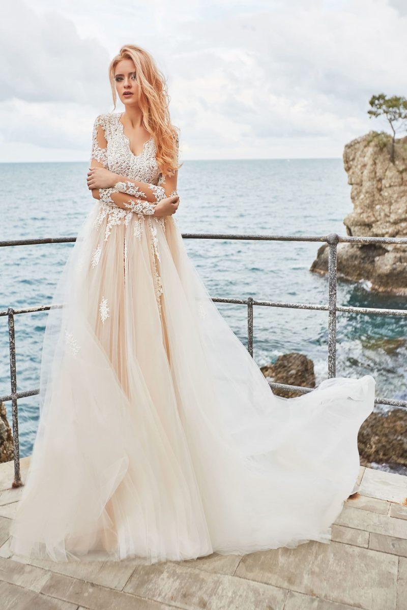 Пудровое свадебное платье с кружевным декором верха и объемной юбкой.