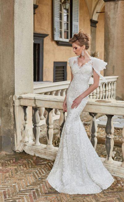Подчеркивающее фигуру свадебное платье с кружевной отделкой и рукавом.