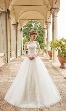 Пышное свадебное платье с вырезом «бато» и длинными рукавами.