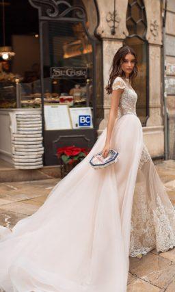 Свадебное платье с пышной верхней юбкой и коротким рукавом.