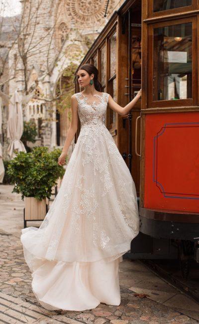 Свадебное платье кремового цвета с коротким рукавом и великолепным шлейфом.