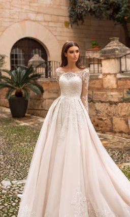 Кремовое свадебное платье с портретным вырезом и длинным рукавом.