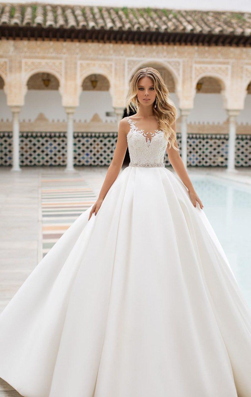 Свадебное платье с пышной атласной юбкой и кружевом на лифе.