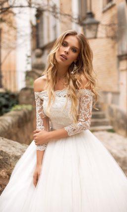 Свадебное платье с портретным декольте и многослойным низом.