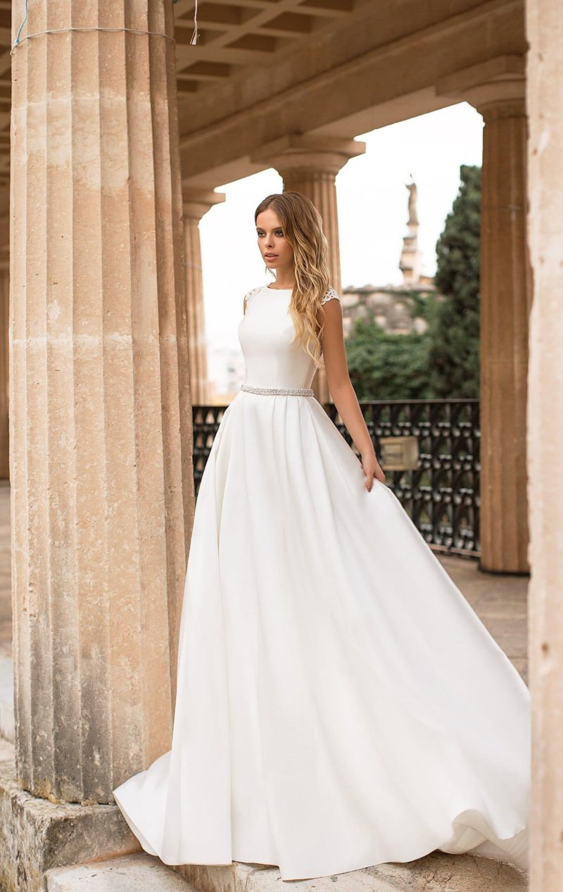 Роскошное свадебное платье с кружевным рукавом и открытой спиной.