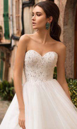 Пышное свадебное платье с открытым лифом, декорированным бисером.