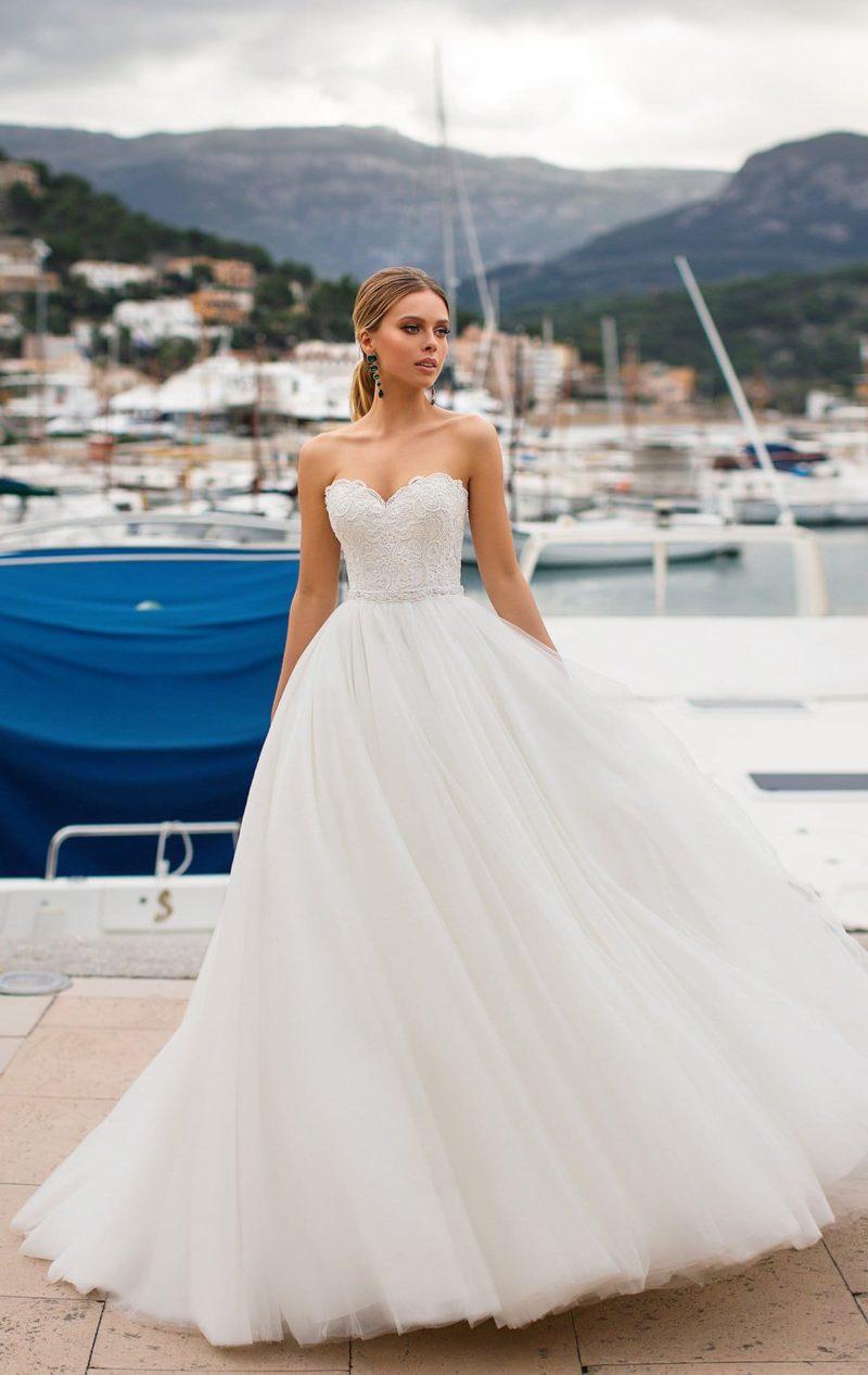 Выразительное свадебное платье с пышным силуэтом и фигурным вырезом.