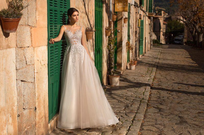 Романтичное свадебное платье с многослойной юбкой и тонкими вставками на лифе.