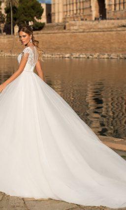 Женственное свадебное платье с коротким рукавом и пышным шлейфом.