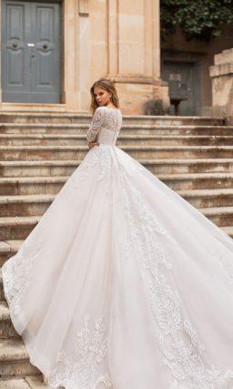 Выразительное свадебное платье пышного силуэта с длинным рукавом.