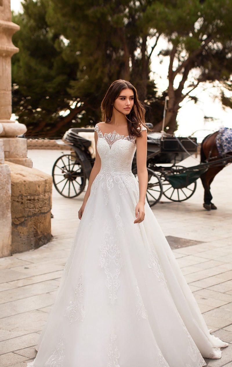 Свадебное платье с аппликациями, украшающими лиф и спинку.
