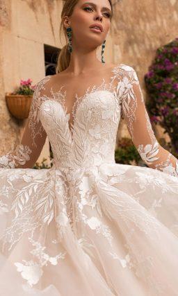 Свадебное платье цвета слоновой кости с длинным полупрозрачным рукавом.