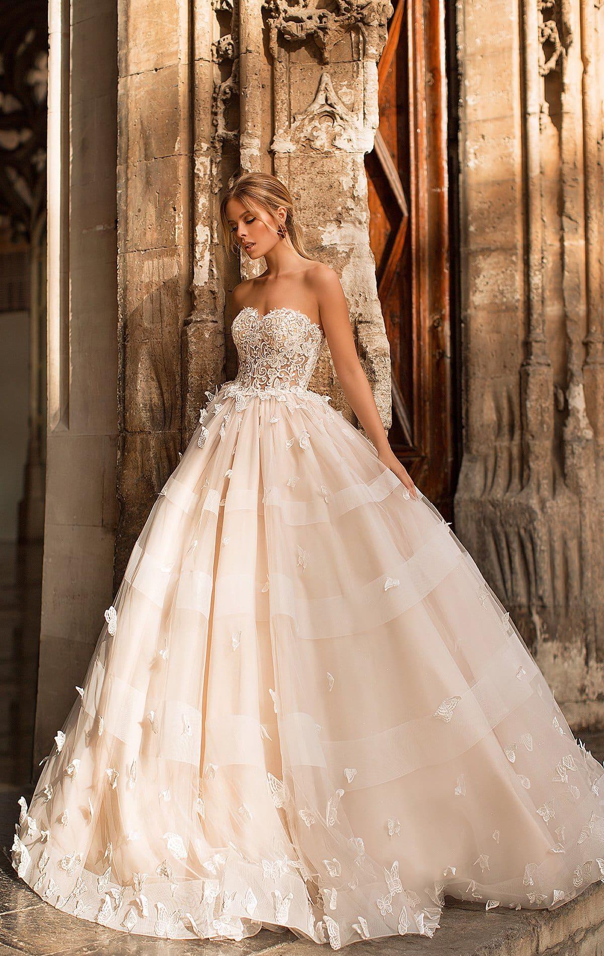 Открытое свадебное платье пышного кроя с объемным декором подола.