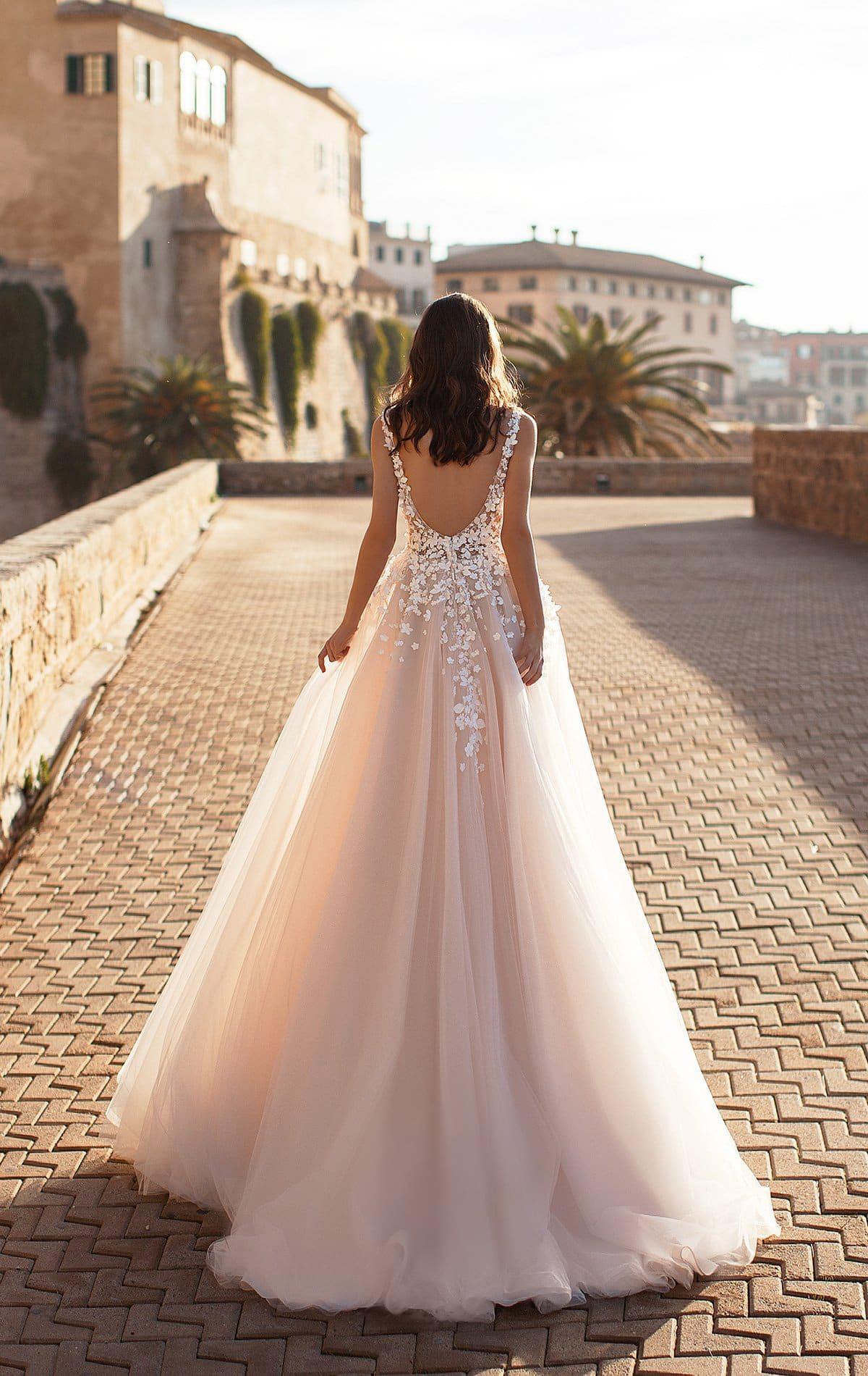 Пудровое свадебное платье с многослойной юбкой и открытой спиной.