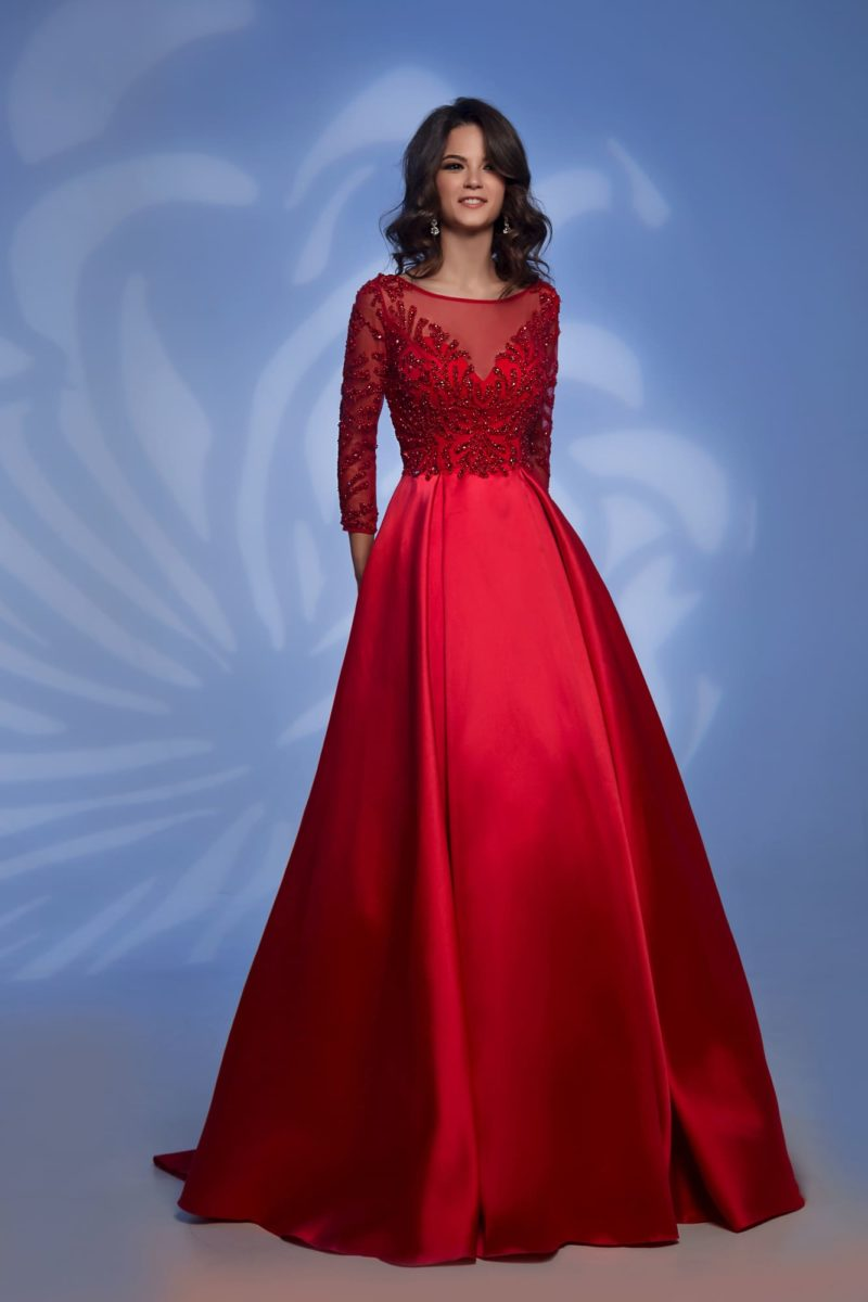 Красное вечернее платье с объемной юбкой и длинным рукавом.