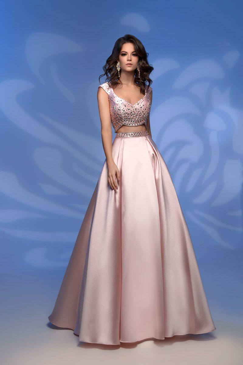 Длинное вечернее платье розового цвета с открытой линией талии.