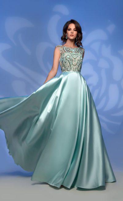 Атласное вечернее платье зеленого цвета с сияющим лифом.
