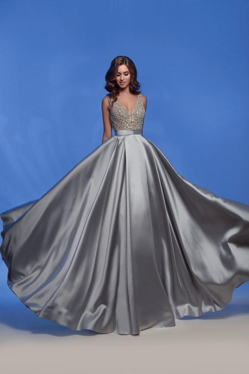 Вечернее платье в пол из серебристого атласа, с глубоким вырезом.
