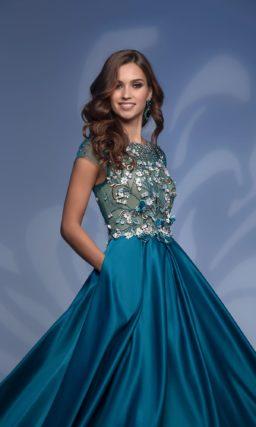 Вечернее платье зеленого цвета с полупрозрачным оформлением верха.