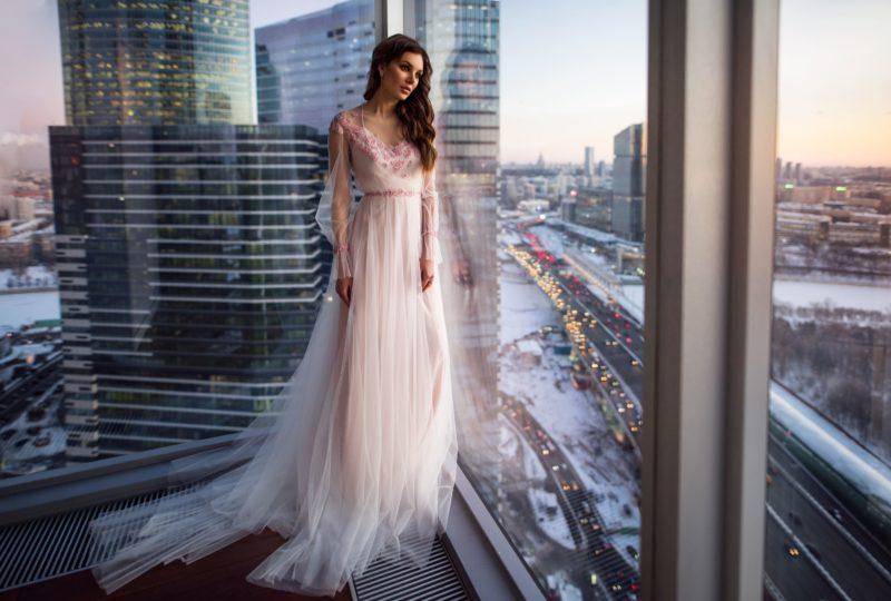 Свадебное платье розового цвета с длинным прозрачным рукавом.