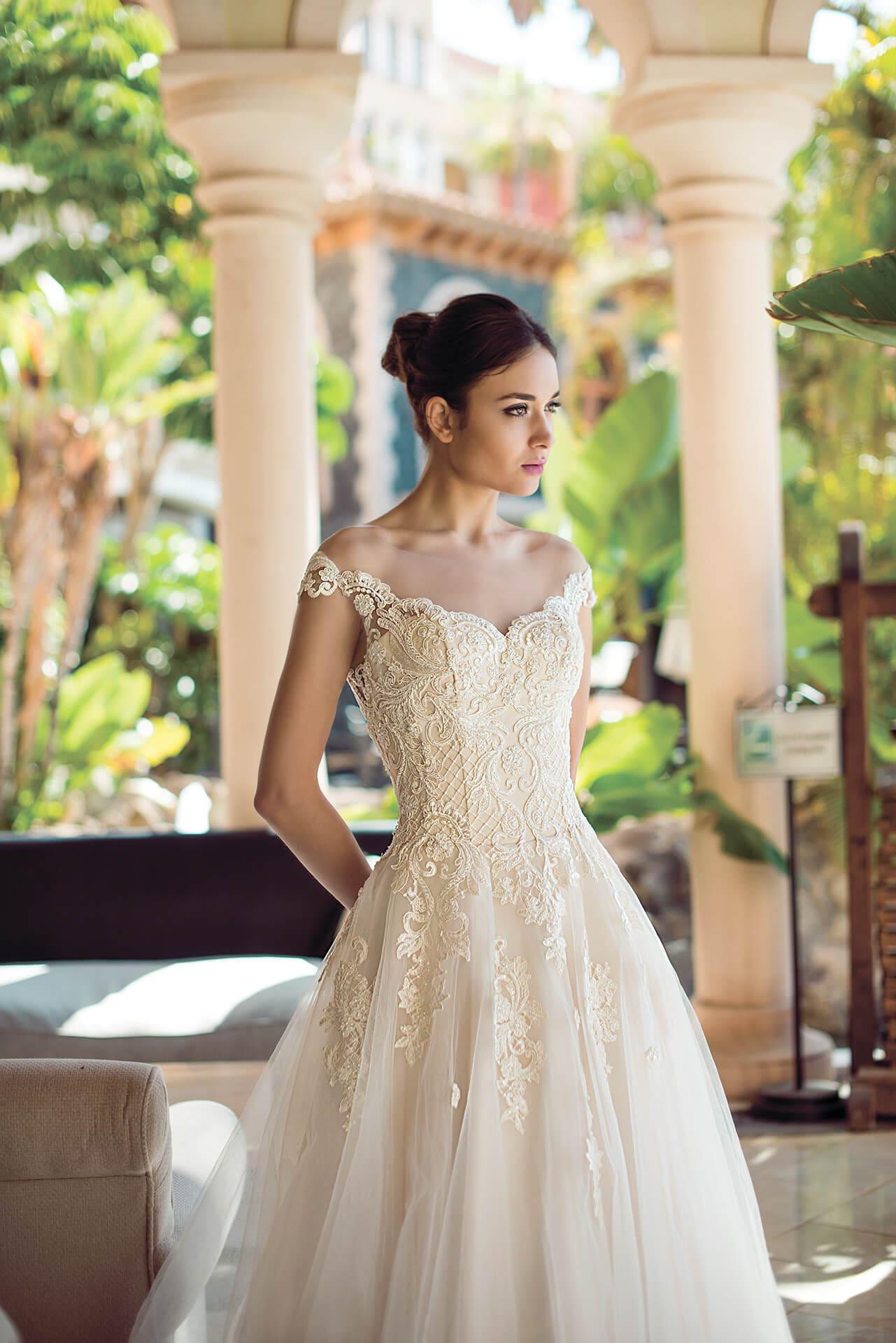 Свадебное платье с многослойным подолом и тонкими кружевными бретелями.