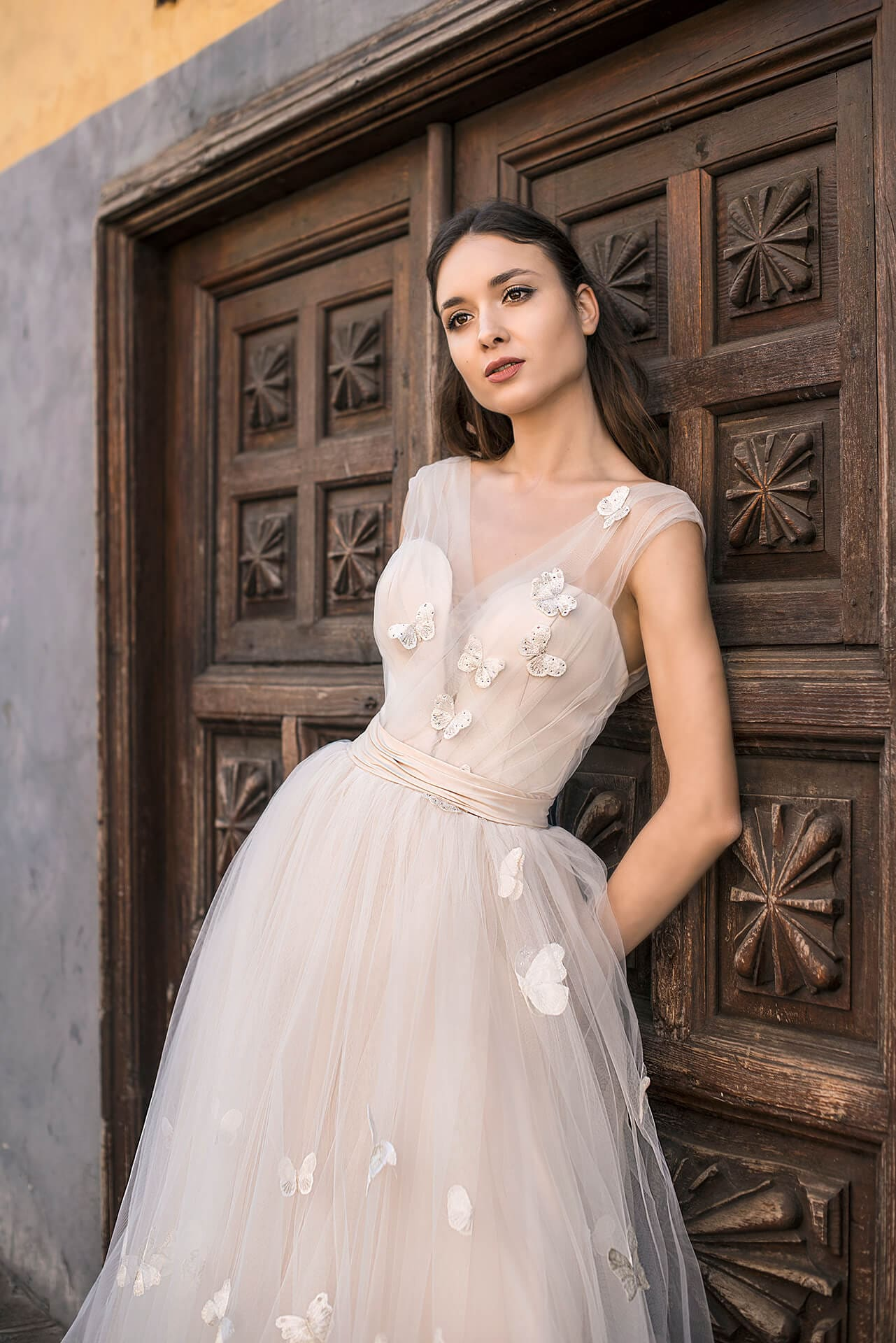 Свадебное платье с вырезом сзади и объемным декором подола.