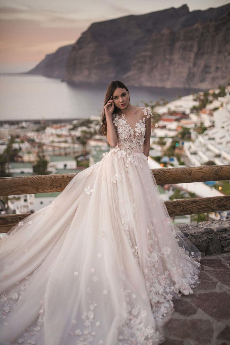 Чарующее свадебное платье с объемным декором и длинным шлейфом.