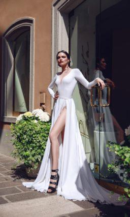 Свадебное платье из атласной ткани, с вырезом на юбке и рукавом.