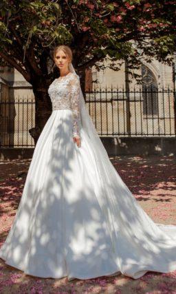 Пышное свадебное платье с длинным рукавом и сияющим поясом.