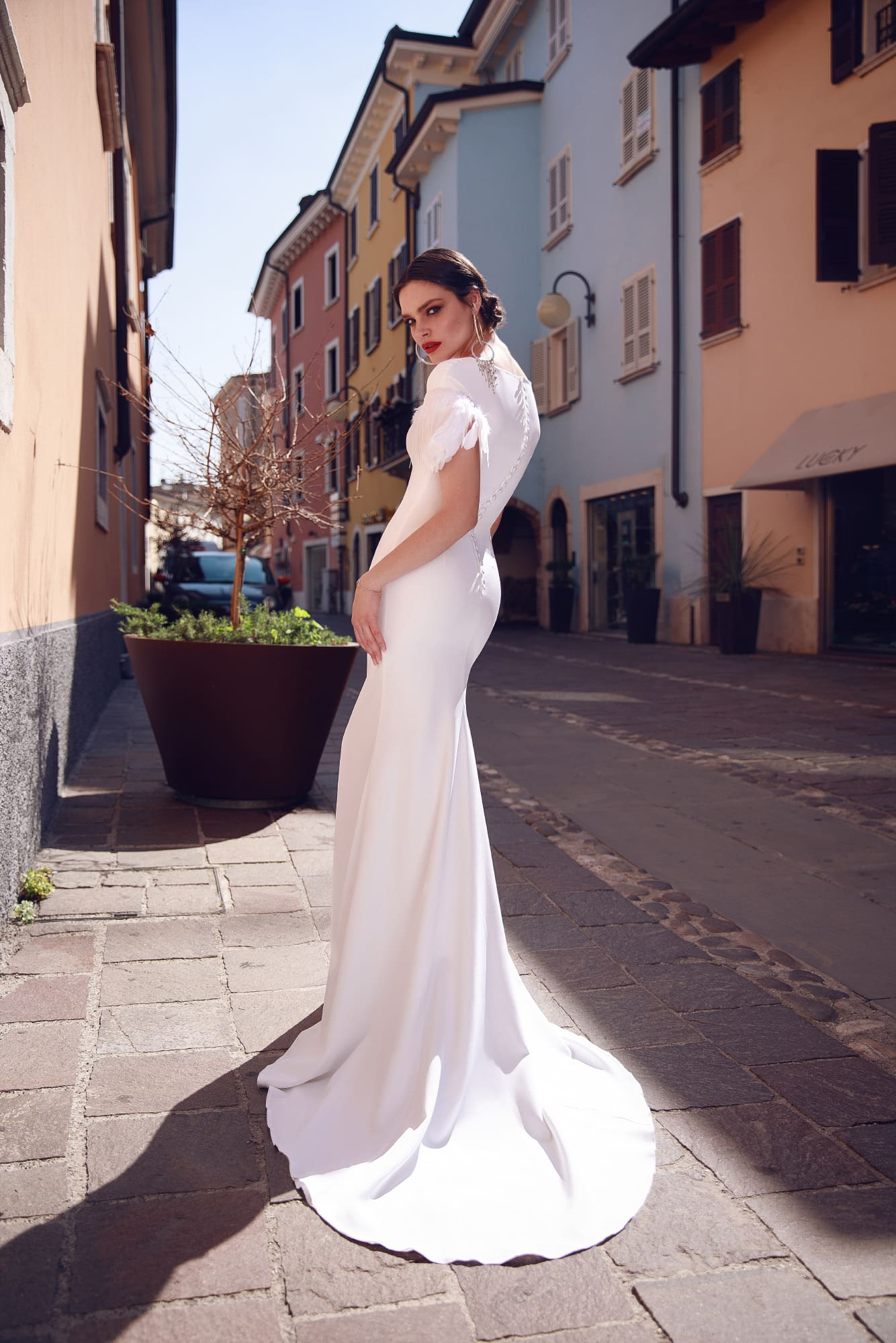 Атласное свадебное платье «русалка» с перьями на коротких рукавах.