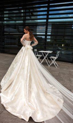 Пышное свадебное платье с атласной юбкой и длинным рукавом.
