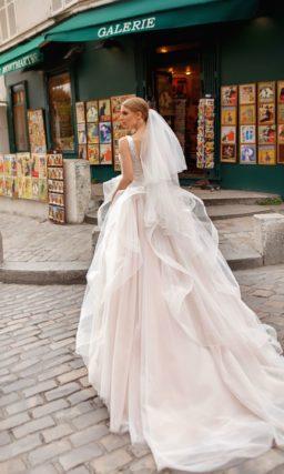 Свадебное платье с оборками на юбке и V-образным вырезом.