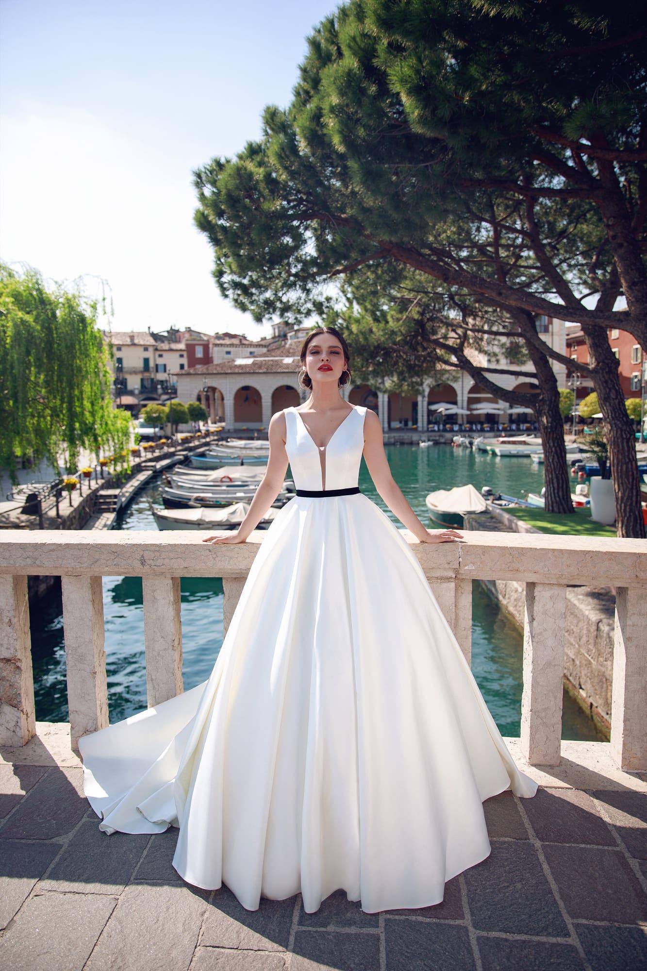 Пышное свадебное платье с черным поясом и глубоким вырезом.