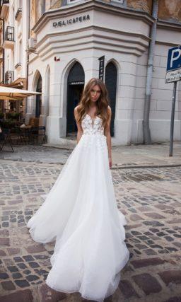 Романтичное свадебное платье с открытым верхом и пышным шлейфом.