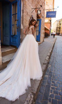 Пышное свадебное платье кремового оттенка с длинным рукавом.